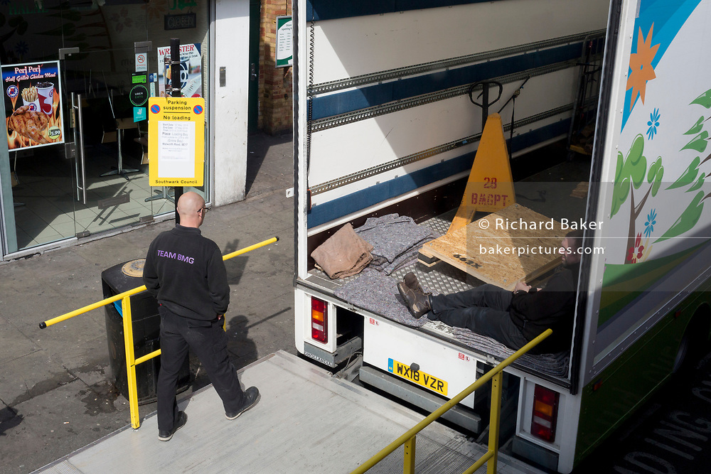 Retail delivery men wait at the back of their open lorry on the Walworth Road in Southwark, south London, on 7th May 2019, in London, England.