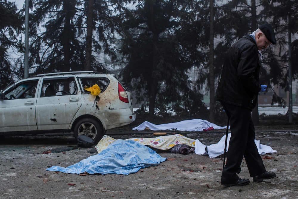 DONETSK, UKRAINE - JANUARY 30, 2015: An investigator walks past the bodies of four people who were killed when a rocket struck the parking lot outside a center where humanitarian aid was being distributed in Donetsk, Ukraine. A fifth person was killed in a parked car, and at least two others died in a separate shelling nearby. CREDIT: Brendan Hoffman for The New York Times