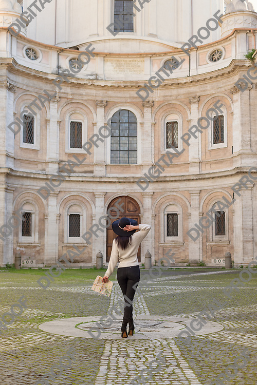 Female traveler fashion concept. Outdoor portrait of  beautiful fashionable lady visiting momuments in Rome.. Model wearing stylish hat and clothes. Sunny day. Back view. Waist up.