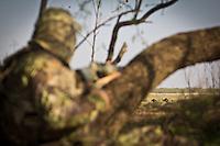TURKEY HUNTER WEARING REALTREE MAX-1 CAMO WATCHING TURKEYS IN A FIELD