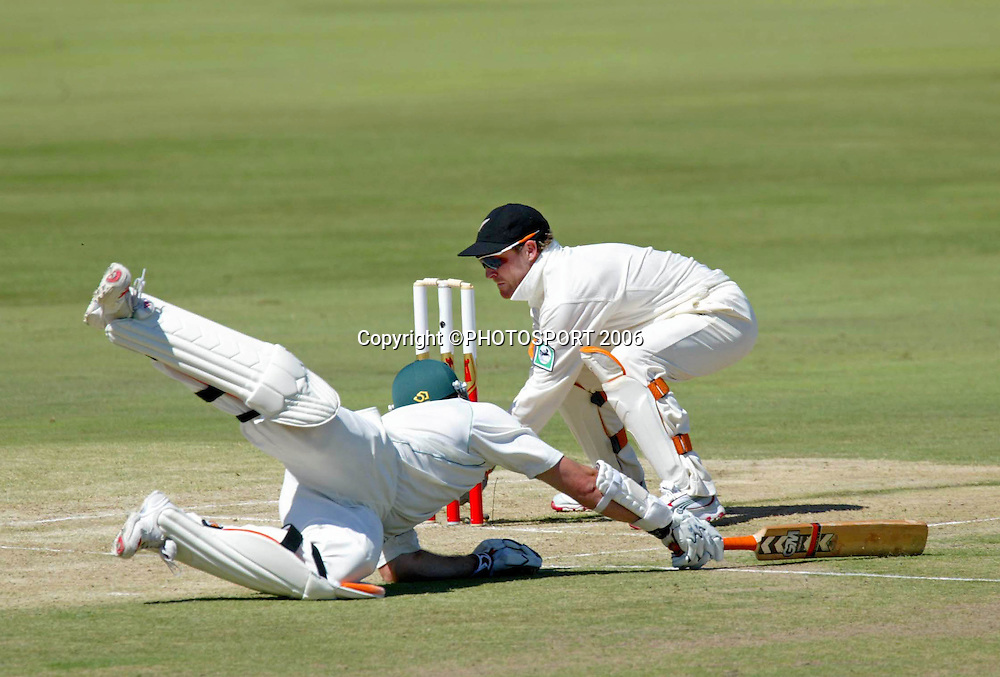 South African captain Graeme Smith dives back into his crease as Brendon McCullum attempts to run him out during day one of the first cricket test between South Africa and New Zealand at SuperSport Park, Centurion, South Africa on Saturday 15 April, 2006. Photo: Africa Visuals/PHOTOSPORT**NZ USE ONLY**<br /> <br /> 150406