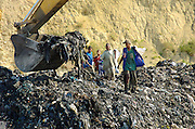 Teens and young kids wait for the backhoe to uncover small shards of metal. They scramble down the sides of the pit and grab the metal.