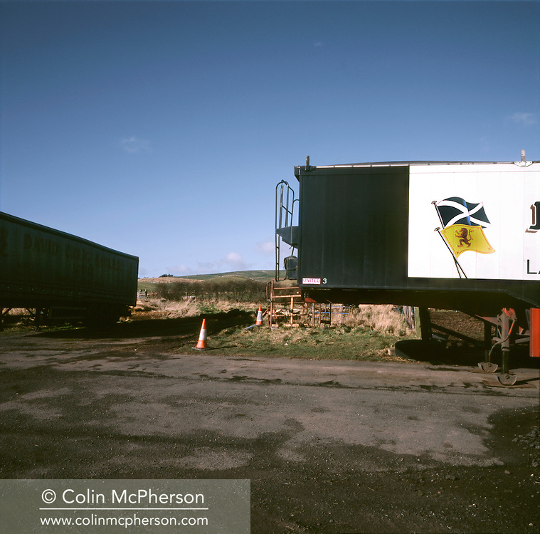 'Haulage business, Lamberton, 2014' from 'A Fine Line - Exploring Scotland's Border with England' by Colin McPherson.<br /> <br /> Scottish flags on a articulated lorries parked in a haulage business a mile from the border with England.<br /> <br /> The project was a one-year exploration of the border between the two historic nations, as seen from the Scottish side of the frontier.<br /> <br /> Colin McPherson is a photographer and visual artist based in north west England. In 2012 he was one of the founding members of Document Scotland, a collective of four Scottish documentary photographers brought together by a common vision to witness and photograph the important and diverse stories within Scotland at one of the most important times in our nation's history.<br /> <br /> 'A Fine Line' will be shown for the first time in public at Impressions Gallery, Bradford, from July 1 until September 27, 2014 to coincide with the Scottish Independence referendum.