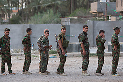 © Licensed to London News Pictures. 29/06/2014. Khanaqin, UK Khanaqin, Iraq. Kurdish peshmerga fighters stand in line for dinner at a Kurdish peshmerga base in Khanaqin, Iraq.<br /> <br /> The peshmerga, roughly translated as those who fight, is at present engaged in fighting ISIS all along the borders of the relatively safe semi-automatous province of Iraqi-Kurdistan. Though a well organised and experienced fighting force they are currently facing ISIS insurgents armed with superior armament taken from the Iraqi Army after they retreated on several fronts. Photo credit : Matt Cetti-Roberts/LNP