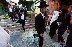 © Licensed to London News Pictures. 02/05/2014. Jerusalem, Israel. Young jewish men hurry past muslim women through the Muslim Quarter of the Old City of Jerusalem at approx 6.30pm in order to reach The Western Wall  in time for the start of the Shabbat (the Jewish sabbath).  Jewish custom sees the lighting of candles scheduled for 6.39pm this evening, shortly before the sunset when Shabbat commences.  The Western Wall is the most important shrine of the Jewish faith and is located in the Old City at the foot of the western side of Temple Mount.  The Old City is comprised of four Quarters - the Jewish, Muslim, Christian and Armenian. Photo credit : Richard Isaac/LNP