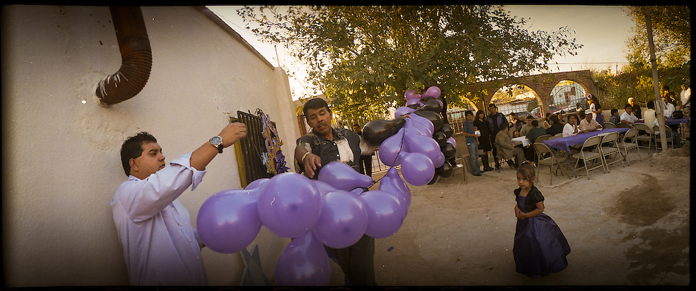 "A father, center, prepares decorations for his daughter's ""Quinceniera"" or 15th birthday party at their family member's home in Ciudad Juarez, Mexico in 2010. The father, who lost his job, spent much of their savings on his daughter's party."
