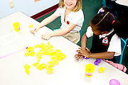 Anastasia Opshal and Sheyan Johnson makes letters out of Play Doh in their kindergarten class at Kennesaw Charter School in Kennesaw, Georgia, April 1, 2010. The 440-student school, which used to be managed by Imagine Schools, is now self-managed.