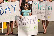 A young girl holds up a sign in support of rescued sea turtles during the release of rehabilitated sea turtles August 6, 2014 in Isle of Palms, South Carolina. The turtle which is critically endangered accidentally swallowed a fishing hook and had it surgically removed by the sea turtle hospital at the South Carolina Aquarium in Charleston.
