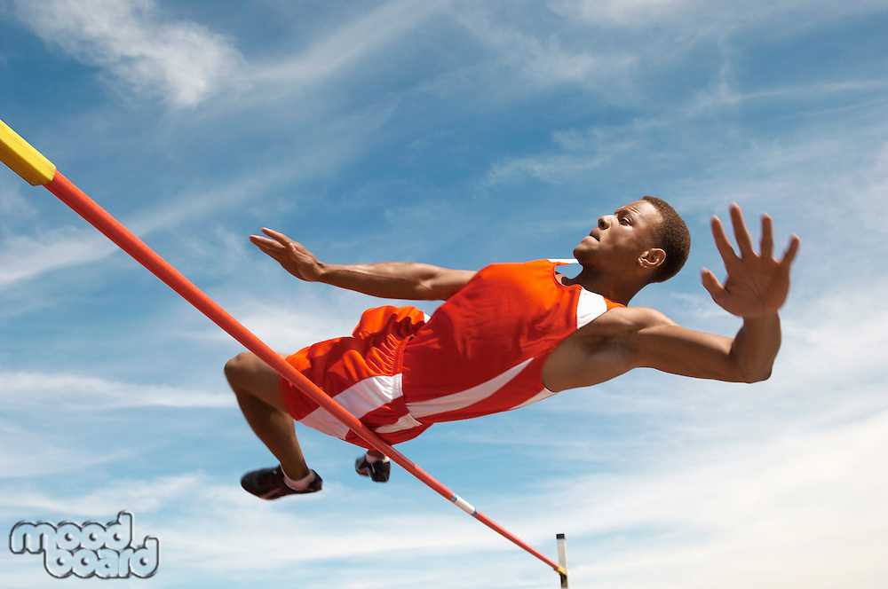 High Jumper in mid air over bar low angle view