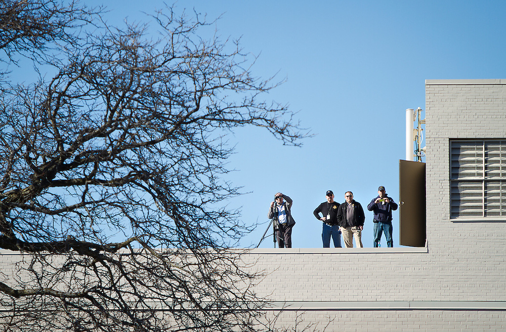Employees in the Department of Corrections watch from the roof as protestors gather around the building in Madison, March 11, 2015. Protestors rallied for the fifth day in a row, after the shooting death of Tony Robinson, Jr. by Madison Police inside his home on March 6, 2015. REUTERS/Ben Brewer (UNITED STATES)