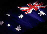 Australian flag coming out of dark background.<br /> <br /> Larger JPEG + TIFF images available by contacting use through our contact page at : www.effectiveworkingimage.com