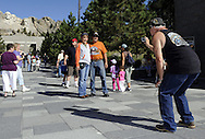 STURGIS, SOUTH DAKOTA - AUGUST 2010:  Motorcyclists pose for a photo at Mount Rushmore while attending the 70th annual Sturgis Motorcycle Rally.  The attendance estimates were placed between 500, 000 and 700,000 bikers.