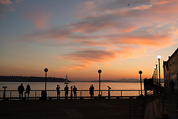 United States, Washington, Seattle, people on pier overlooking Elliott Bay  and the Olympic Mountains at sunset