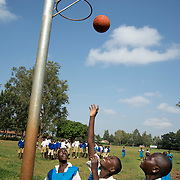 Kenya. Siaya. Agoro Oyombe Primary . Linnet Aoko Ogola, 16 years old, speech and language disorder and mild cerebral palsy playing netball with her friend Mary Otieno