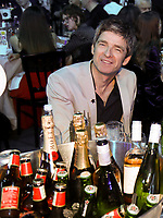 Noel Gallagher having a drink at his table