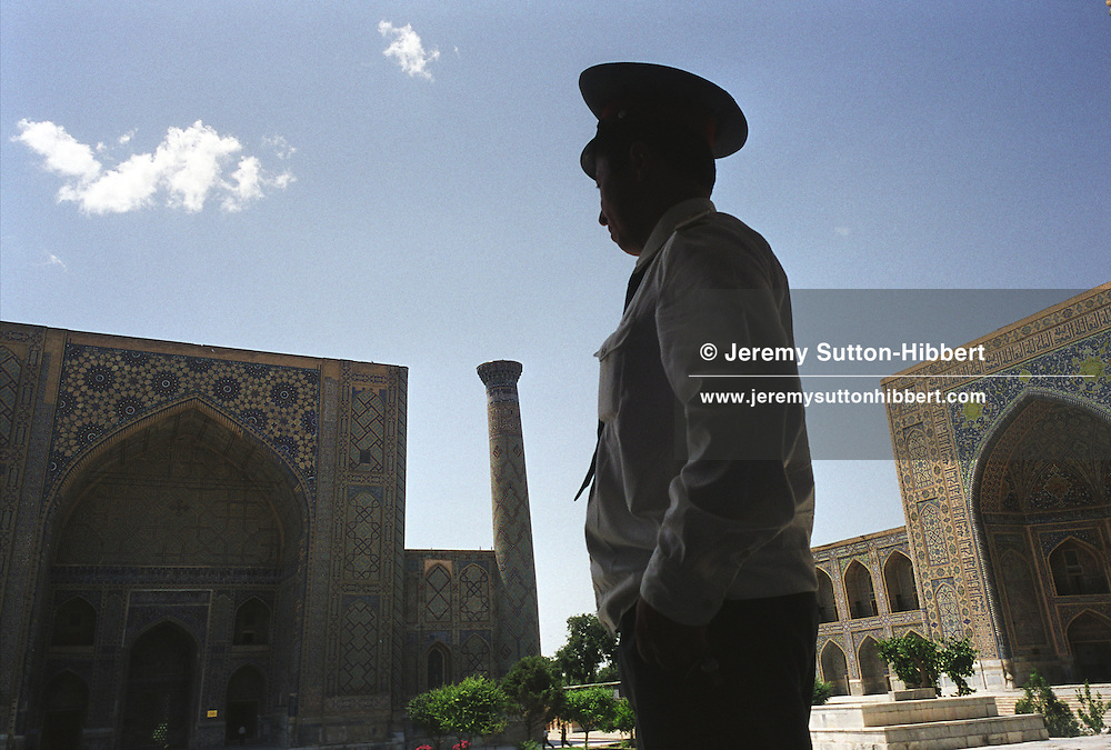 A security guard watches over the Ulughbek Medressa, on left of picture, and the 17th century Tilla-Kari Medressa, on right of picture, once important Islamic studies teaching schools, now a tourist destination in Registan Square, Samarkand, Uzbekistan. The city was once an important part of the old Silk Road trading route through Central Asia.