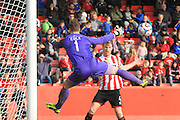 Kyle Storer forces a save from Jake Cole during the Vanarama National League match between Cheltenham Town and Woking at Whaddon Road, Cheltenham, England on 12 March 2016. Photo by Antony Thompson.