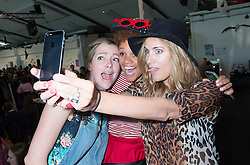 Chelsea Healey, Gemma Cairney and Caroline Flack take a selfie at the Rumble In The Jumble #3, a charity jumble sale hosted by Gemma Cairney at the Oval in Bethnal Green, London, UK, in association with Oxfam in aid of abused women in the Democratic Republic of the Congo. <br /> <br /> Saturday, 26th April 2014.<br /> Picture by Ben Stevens / i-Images