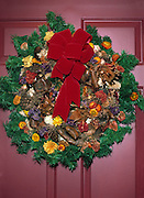 Christmas wreath with straw flowers on maroon door; holiday decorations; colorful
