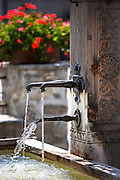 Tap and water fountain in Serneus near Klosters in Graubunden region, Switzerland