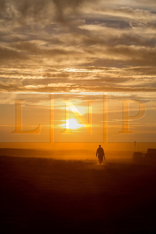 © Licensed to London News Pictures. 08/10/2014.  British Army Training Unit Suffield (BATUS), Canada. A soldier returns to his vehicle as a military exercise in Canada comes to an end.  <br /> <br /> BATUS has been home to the Army for the past 42 years.  It is the only place where all elements of the British Army train together for war.  The soldiers are put to test on everything from armoured vehicles to infantry tactics.        Photo credit : Alison Baskerville/LNP
