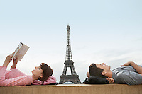 Couple lying on ledge of the Trocadero with Eiffel Tower viewed in the background