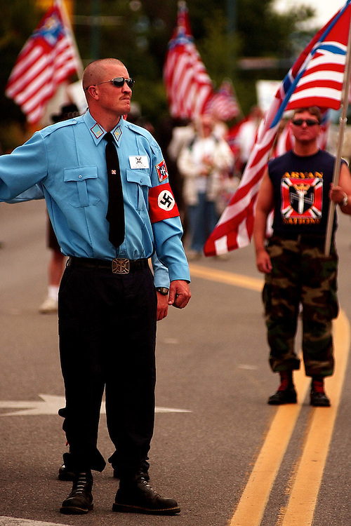 COEUR D ALENE, ID - JULY 17:  An Aryan Nation's security guard walks along Sherman Avenue route during World Congress Parade held in Coeur d'Alene, Idaho, on Saturday, July 17, 2004. About 40 supporters and members marched in downtown Coeur d'Alene for the Aryan World Congress. (Photo by Jerome Pollos/Getty Images)