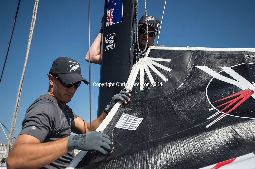 Emirates Team New Zealand sailors Blair Tuke and Glenn Ashby guide the main sail up before racing on day two of the Extreme Sailing Series at Nice. 3/10/2014. Photo: Chris Cameron/www.photosport.co.nz