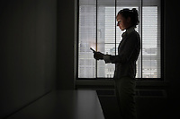 Female office worker standing using mobile phone in darkened office side view