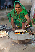 Vasanben making chapatis on an open wood fire at their home in Ahmedabad, India. making chapatis on an open wood fire at their home in Ahmedabad, India.