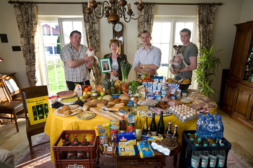 Family of Carlo and Marie Paule Kutten-Kass, Luxembourg with one week's worth of food. Photographed in their dining room. MODEL RELEASED. Carlo and Marie Paule Kutten-Kass of the town of Erpeldange in Bous, southeast of Luxembourg City, near the German border. Carolo is 49. Marie Paule is 48. Also in the photograph: their sons Joe, 19, and Georges, 22. Their daughter was away during the time the photograph was made. Grand Duchy of Luxembourg.