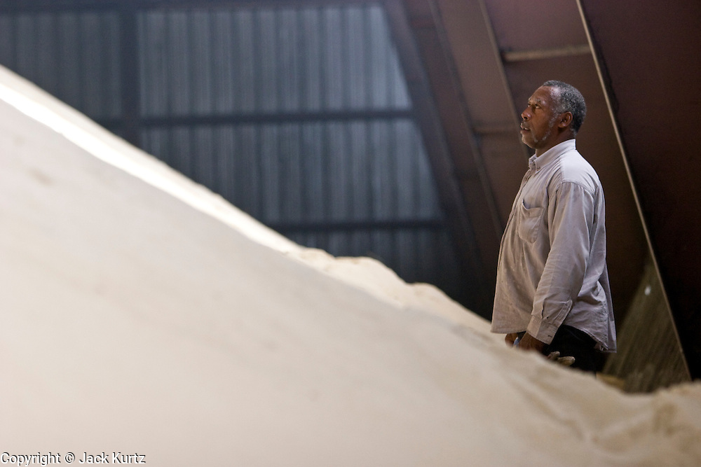 15 NOVEMBER 2005 - FRANKLIN, LA: JOSEPH AUGUST checks on raw sugar in the warehouse at the St. Mary Sugar Co-Op Mill near Franklin, Louisiana during the 2005 sugar cane harvest. Sugar mills across Louisiana are being forced to warehouse tens of millions pounds of raw sugar because the sugar refineries in New Orleans are closed because of damage from Hurricane Katrina. The refineries are scheduled to reopen in late 2005. Louisiana is one of the leading sugar cane producing states in the US and the economy in southern Louisiana, especially St. Mary and Iberia Parishes, is built around the cultivation of sugar. The mill employs about 180 people. The two mills near Franklin contribute about $150 million (US) to the local economy. Sugar growers in the area are concerned that trade officials will eliminate sugar price supports during upcoming trade talks for the proposed Free Trade Area of the Americas (FTAA). They say elimination of price supports will devastate sugar growers in the US and the local economies of sugar growing areas. They also say it will ultimately lead to higher sugar prices for US consumers. PHOTO BY JACK KURTZ