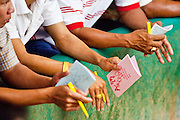 10 APRIL 2010 - PLA PAK, NAKHON PHANOM, THAILAND: Wagerers keep track of the cock fights in notebooks. Cockfighting is enormously popular in rural Thailand. A big fight can bring the ring operator as much as 200,000 Thai Baht (about $6,000 US), a large sum of money in rural Thailand. Fighting cocks live for about 10 years and only fight for 2nd and 3rd years of their lives. Most have only four fights per year. Fighting cocks in Thailand do not wear the spurs or razor blades that they do in some countries and most times the winner is based on which rooster stops fighting or tires first rather than which is the most severely injured. Although gambling is illegal in Thailand, many times fight promoters are able to get an exemption to the gambling laws and a lot of money is wagered on the fights. Many small rural communities have at least one cockfighting arena.   PHOTO BY JACK KURTZ