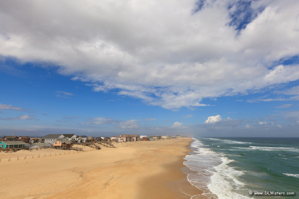 Photograph of Nags Head beach taken from Jennette's Pier on a sunny day with scattered clouds.