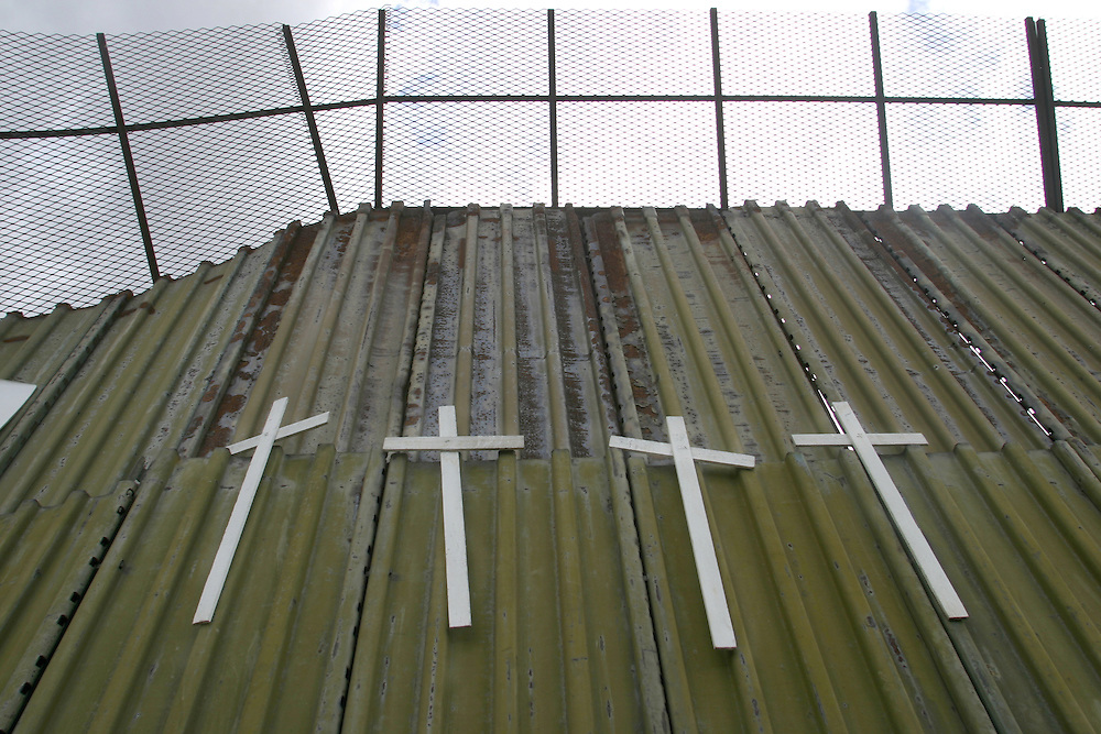 Crosses are hung on the border wall with names of people who died trying to cross the desert to enter the United States on the Mexican side of the border town of Nogales, which straddles the US-Mexican border, on 16 July 2006.