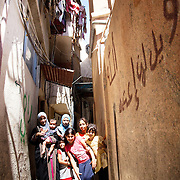 In Ein El-Hilweh refugee camp, home to 75.000 Palestinians. Mother Hannan with some of her 6 children in the alley outside her front door. They live in a two room flat, the father Ali sells watermellons in the street. Most of the children receive psychosocial help to relieve them from stress and Naba'a's psychologist Rouda Ismael has been visiting them for years. With her help 15 year old Muhammed can now walk and Doaa can now speak. Developmental Action Without Borders(Naba'a) work in Palestinian refugee camps across Lebanon to help children in the camps.  The camps are densely over-crowded and many of the children are 4th generation refugees living in Lebanon with no citizenship or rights and under immense pressure. Naba'a is a mix of Palestinians and Lebanese and aim to give children a sense of security and freedom to express their needs and rights.Naba'a operates in communities governed by a multitude of political parties and religious groups and Naba'a keeps a strict independed line from any affiliation with any groups.