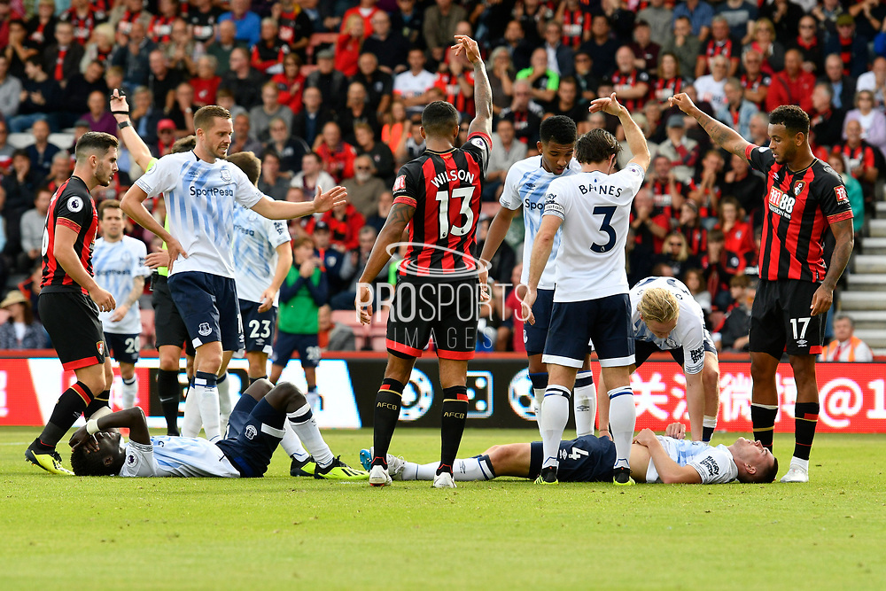 Players and officials wave desperately to get the medics on after Michael Keane (4) of Everton sustains a head injury after Idrissa Gueye (17) of Everton colided with him during the Premier League match between Bournemouth and Everton at the Vitality Stadium, Bournemouth, England on 25 August 2018.