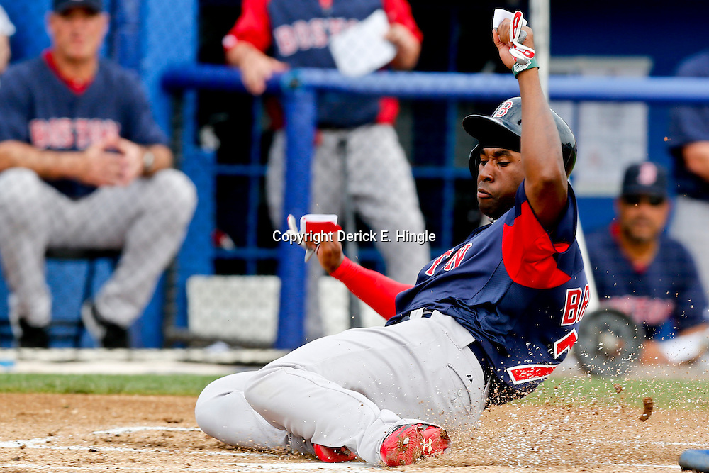 Feb 25, 2013; Dunedin, FL, USA; Boston Red Sox center fielder Jackie Bradley (74) slides home on a pass ball by Toronto Blue Jays starting pitcher R.A. Dickey (not pictured) during the top of the first inning of a spring training split squad game at Florida Exchange Park. Mandatory Credit: Derick E. Hingle-USA TODAY Sports
