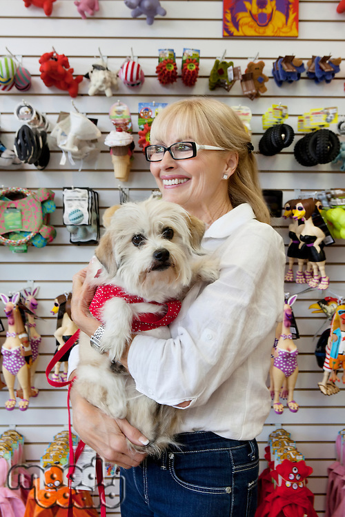 Senior pet shop owner standing with dog