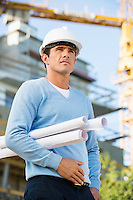 Male architect with rolled up blueprints standing at construction site