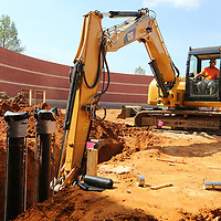Danuel Crossen, an employee with Fireline of Tupelo, uses a backhoe to fill and pack dirt around the main lines of the sprinkler system that he and his crew are installing during the construction of the new gymnasium at Tupelo High School on Wednesday.