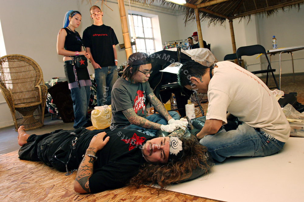 A couple of Indonesian tattoo artists are working using traditional methods at the 2nd International Tattoo Convention in London on Saturday, Oct. 7, 2006, in London, UK. With over 15.000 visitors in three days during the 2005 edition, the event placed London in a central position in the tattoo world.  This year about 150 artists ,representing all the tattoo styles, are ticking away with their machines in a very exciting atmosphere. **ITALY OUT**....