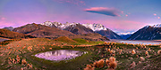 Pre dawn alpenglow, sheep grazing, panorama reflection in small pond, Canterbury high country, Reishek  Mountains, Rakaia Valley, New Zealand.