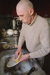 Hostel resident washing up dishes after communal meal in homeless hostel for people with learning difficulties,
