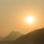 A lone wooden sampan is silhouetted against the sunset on the Mekong River near Luang Prabang, Laos. Copyspace.
