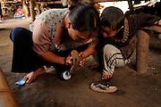 Kachin refugee housewives ai Je Yang Hka near China Myanmar boarder Lai Za, help her son to mend the torn slipper.