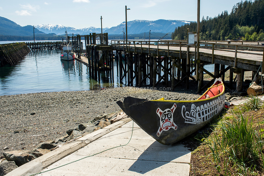 Ornately painted wooden canoe in front of a dock in Alert Bay, BC.