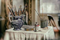 Paintbrushes in a pitcher with oil paint tubes on a table.
