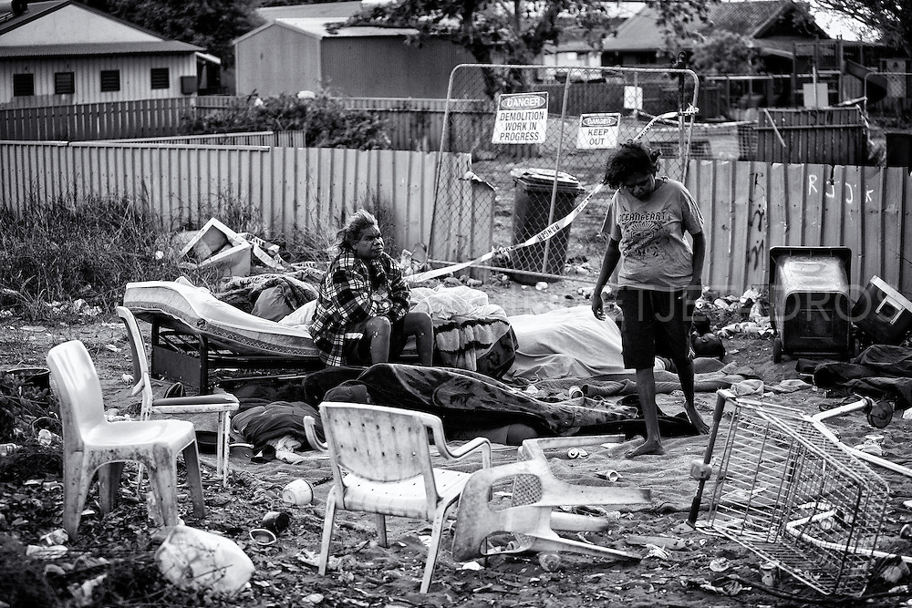 Sussanne Charmawina and Jacquelin waking up in their new camp, at the other side of the fence, as the condemned house they used before in Kennedy Hill, has now been demolished. Till this day this camp is still being used by many homeless people. Broome, Western Australia. ©Ingetje Tadros/Diimex