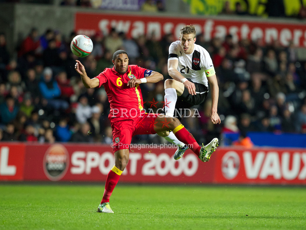 SWANSEA, WALES - Wednesday, February 6, 2013: Wales' Ashley Williams in action against Austria's Marc Janko during the International Friendly at the Liberty Stadium. (Pic by Kieran McManus/Propaganda)